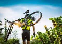 Cyclist raises the mountain bikes on their shoulders. - stock photo