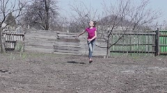 Happy girl running down the village yard Stock Footage