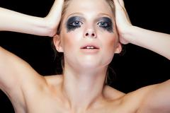 Beauty portrait of woman with black messed make up - stock photo