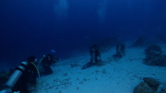 Group of divers watching swimming in lagoon entrance channel with Reef manta ray Stock Footage