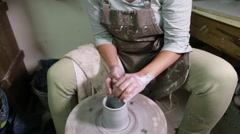 Potter at work creating clay bowl on turning wheel Stock Footage