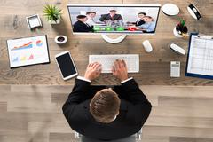 Young Businessman Attending Video Conference On Computer At Office - stock photo