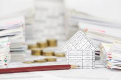 House and pencil with blur coins between overload of paperwork - stock photo
