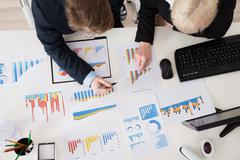 High Angle View Of Two Young Businesspeople Analyzing Financial Graphs Stock Photos