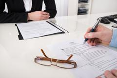 Close-up Of Businessperson With Resume And Pen In Office Stock Photos
