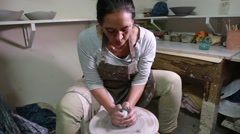 Potter works with clay to model a new vase Stock Footage