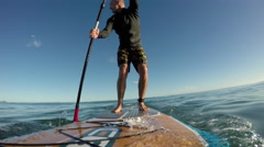Stand up paddle board (SUP) surfing on scenic beach Stock Footage