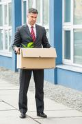 Stock Photo of Sad Mature Businessman Carrying His Belongings In Box After Being Fired