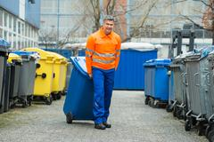 Happy Male Worker Walking With Dustbin On Street During Day Stock Photos
