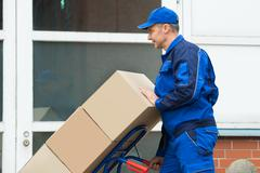 Stock Photo of Mature Happy Delivery Man Carrying Boxes On A Hand Truck On Street