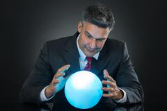 Portrait Of Businessman Predicting Future With Crystal Ball On Desk Stock Photos