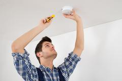 Male Electrician With Screwdriver Repairing Fire Sensor - stock photo