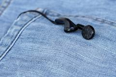 black earbuds in back pocket jeans - stock photo