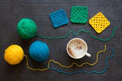 Yarn of three colors, crocheted motives and coffee Stock Photos