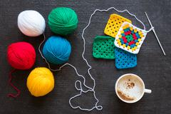 Yarn of five colors, crocheted motifs and coffee - stock photo