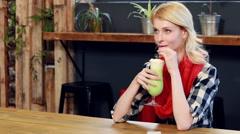 Woman drinking green milkshake - stock footage