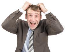 Screaming businessman tearing his hair - stock photo