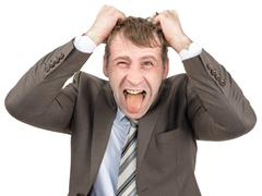 Screaming businessman tearing his hair - stock photo