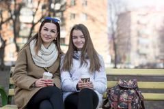 Mother and daughter sitting in autumn or spring park bench, are kept the hands - stock photo