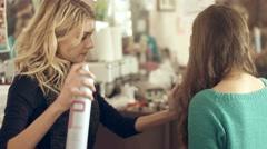 Hairdresser sprays hairspray on the model's hair Stock Footage