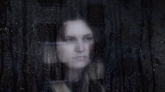 Sad and thoughtful young woman looking out of a window at night. Stock Footage