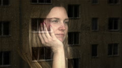Young woman looking out of a window. Feeling abandoned and sad. Stock Footage