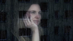 Sad and thoughtful young woman looking out of a window. Stock Footage