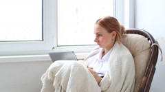 Woman relaxing in a white wicker chair in her living room working on a laptop Stock Footage