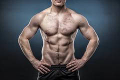 Torso of young man isolated on dark blue background - stock photo