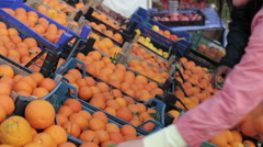 Beautiful woman puts orange in bag out of the box. Large ripe oranges lie in Stock Footage