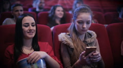 Woman in cinema using mobile Stock Footage