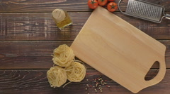 Pasta and ingredients on dark wooden background. Stock Footage