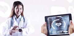 Composite image of asian doctor using her smart watch Stock Photos