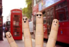 close up of four fingers with smiley faces - stock photo