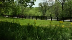 Group of cyclists ride along a country fence line in Kentucky Stock Footage