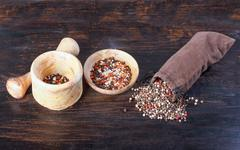 Spices in a sack, bulk spices in a porcelain cup, a spoon, a wooden table. - stock photo
