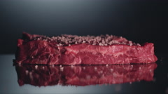 Piece of raw beef steak is cooking with salt and pepper. Close up. Macro lens Stock Footage
