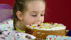 Little Girl Biting into a Birthday Cake - stock footage