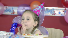 Little Girl Blows into a Noisemaker on her Birthday Stock Footage
