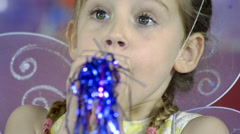Close on Little girl Blowing into a Noisemaker Stock Footage