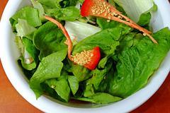 Household biowaste in white plastic bowl, green lettuce, peppers, onions - stock photo