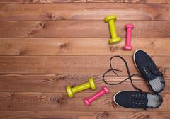 Fitness shoes with heart laces, weights on wooden background Stock Photos