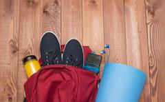 Backpack with sports equipment on wooden floor - stock photo