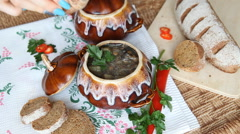 On the russian table is pot with lenten meal. Hand adds pepper to the soup. Stock Footage