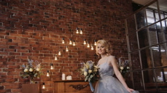 Bride in stylish serenity dress with a bouqet in a loft space - stock footage