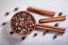 Spices in a wooden bowl, ceramic spoon, pepper, thyme, cinnamon, chili pepper - stock photo