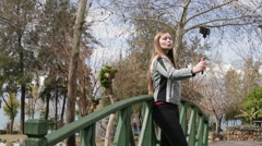 Young happy woman taking self portrait standing on the wooden bridge using - stock footage
