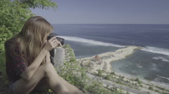 Young woman taking pictures on the edge of a cliff overlooking ocean, ungraded Stock Footage