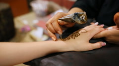 Mehndi. Master makes henna pattern on model's hand Stock Footage