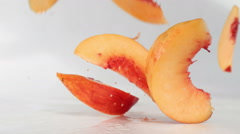 Peach slices falling on a wet surface Stock Footage